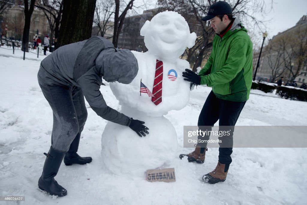 Daphne Kiplinger (L) and her husband Dave Steadman sculpt a 'Snowbama' in Dupont Circle February 13, 2014 in Washington, DC. Up to 12 inches of snow fell over the Washington area causing WMATA to cancel bus service but rail service continued to operate.