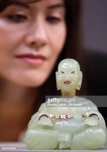Daphne Ruckel an employee at Christie's London looks at the Onassis Faberge Buddha worth 250000 to 350 at a press preview for Christie's Jewels The...