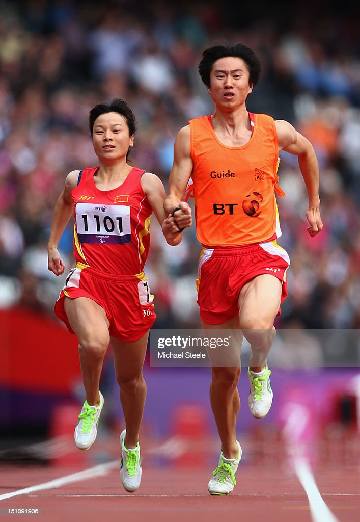 Daqing Zhu of China and her guide ; Hui Zhang compete in the Women's 100m - T12 heats on day 3 of the London 2012 Paralympic Games at Olympic Stadium on September 1, 2012 in London, England.