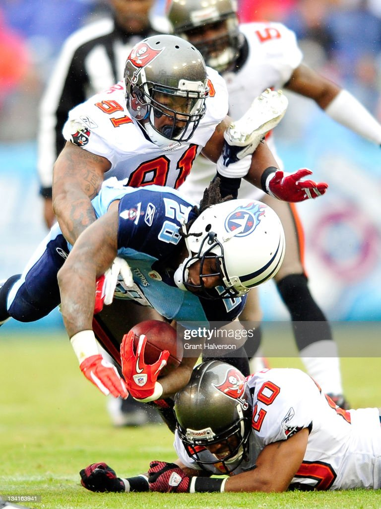 Da'Quan Bowers and Ronde Barner of the Tampa Bay Buccaneers tackles Chris Johnson of the Tennessee Titans during play at LP Field on November 27 2011...