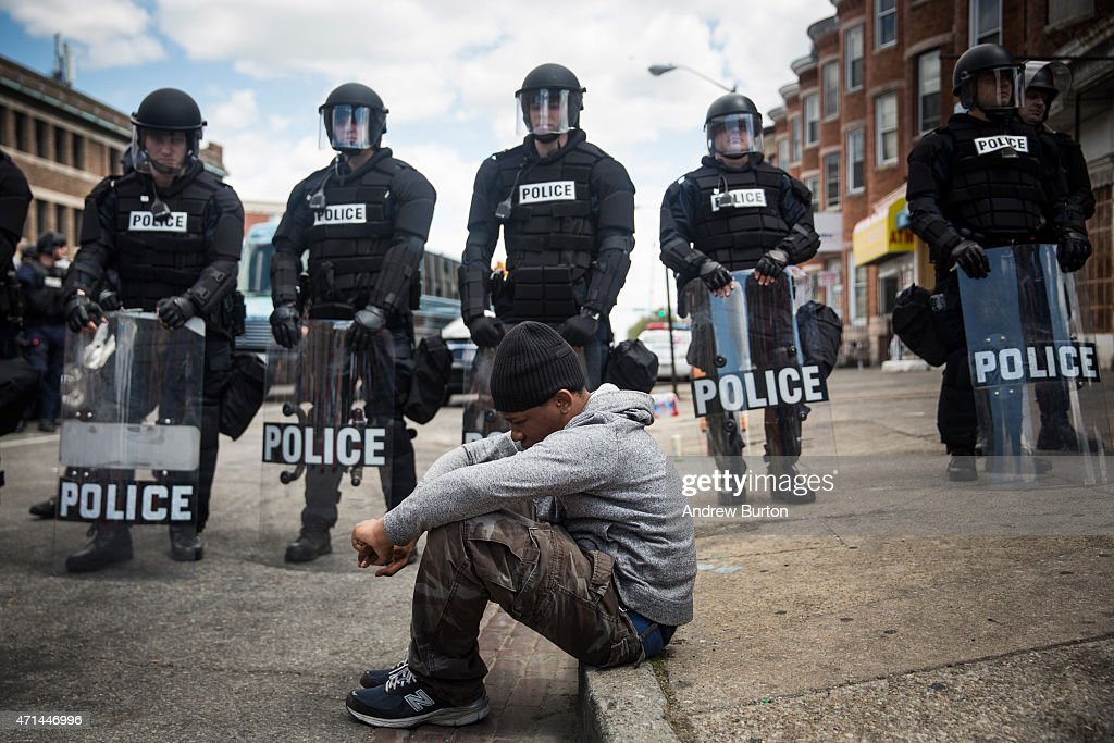 Daquan Green age 17 sits on the curb while riot police stand guard near the CVS pharmacy that was set on fire yesterday during rioting after the...