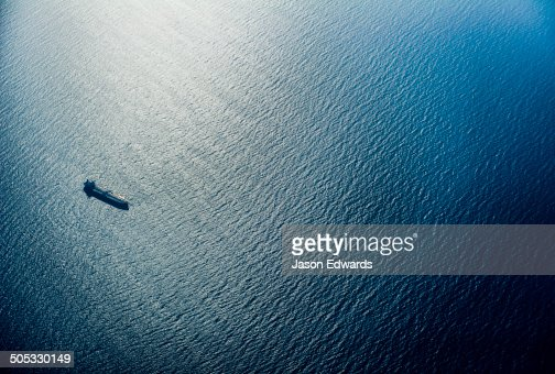 A cargo ship sailing across a vast blue ocean in the late afternoon.