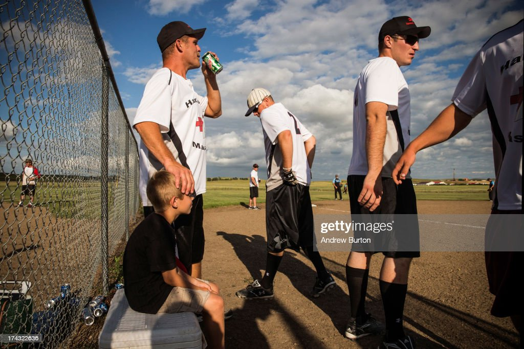 Darby Hanson (L), with his son Jacob Hanson, aged 8, during an organized softball game on July 23, 2013 in Watford City, North Dakota. North Dakota is been experiencing an oil boom in recent years, due in part to new drilling techniques including hydraulic fracturing and horizontal drilling. In April 2013, The United States Geological Survey released a new study estimating the Bakken formation and surrounding oil fields could yield up to 7.4 billion barrels of oil, doubling their estimate of 2008, which was stated at 3.65 billion barrels of oil. Hanson works as in masonry and has lived in Watford City for six years; he says he has seen both good and bad changes. 'Personally, for me it's been good, but it's tough to see things not always done correctly,' Hanson said.