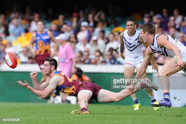 Darcy Gardiner of the Lions handballs during the round 22 AFL match between the Brisbane Lions and the Fremantle Dockers at The Gabba on August 24...