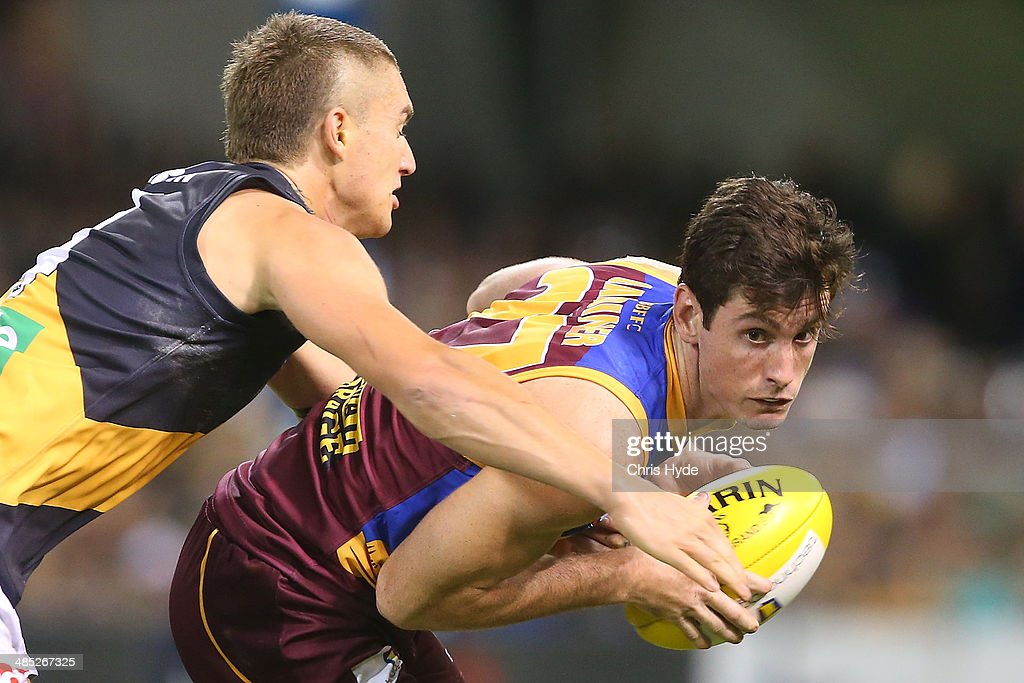 Darcy Gardiner of the Lions is tackled by <a gi-track='captionPersonalityLinkClicked' href=/galleries/search?phrase=Dustin+Martin&family=editorial&specificpeople=5404528 ng-click='$event.stopPropagation()'>Dustin Martin</a> of the Tigers during the round five AFL match between the Brisbane Lions and the Richmond Tigers at The Gabba on April 17, 2014 in Brisbane, Australia.