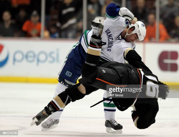 Darcy Hordichuk of the Vancouver Canucks throws George Parros of the Anaheim Ducks to the ground during a fight in the second period at the Honda...