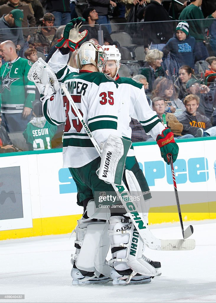 Darcy Kuemper and Nate Prosser of the Minnesota Wild celebrate a win against the Dallas Stars at the American Airlines Center on November 15 2014 in...