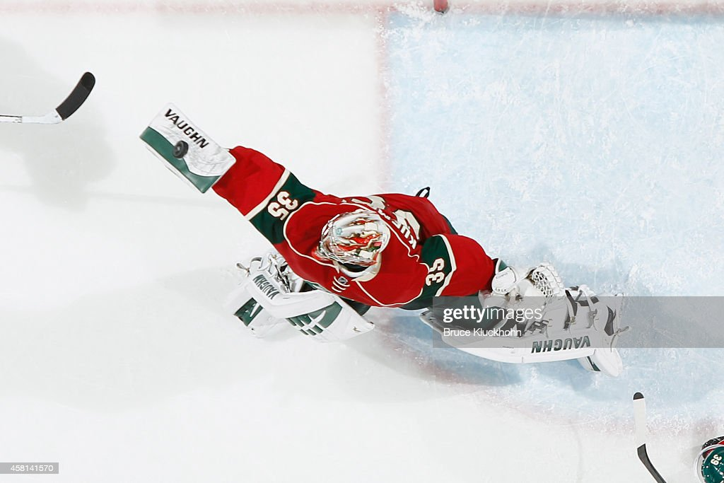 Darcy Kuemper of the Minnesota Wild makes a save against the San Jose Sharks during the game on October 30 2014 at the Xcel Energy Center in St Paul...