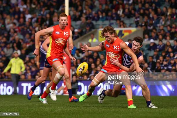 Darcy MacPherson of the Suns and Lachie Neale of the Dockers contest for the ball during the round 20 AFL match between the Fremantle Dockers and the...