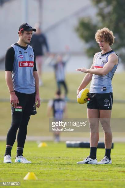Darcy Moore listens to Chris Mayne during a Collingwood Magpies AFL training at the Holden Centre on July 11 2017 in Melbourne Australia