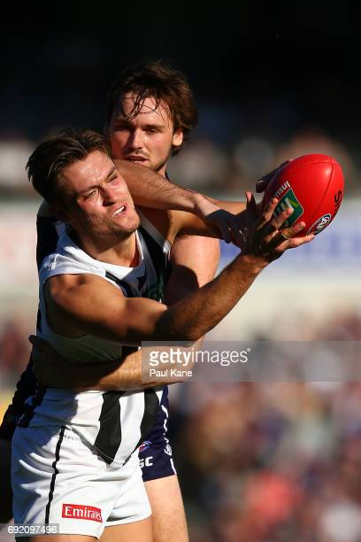 Darcy Moore of the Magpies marks the ball against Joel Hamling of the Dockers during the round 11 AFL match between the Fremantle Dockers and the...