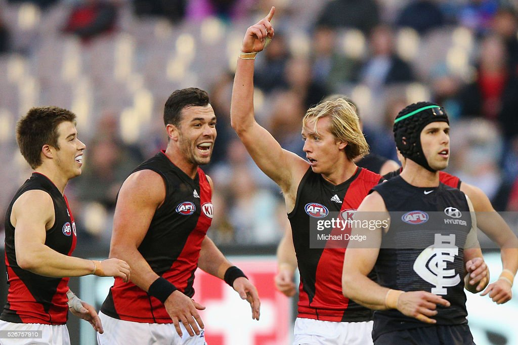 Darcy Parish of the Bombers celebrates a goal with Zach Merrett (L) and Ryan Crowley during the round six AFL match between the Carlton Blues and the Essendon Bombers at Melbourne Cricket Ground on May 1, 2016 in Melbourne, Australia.
