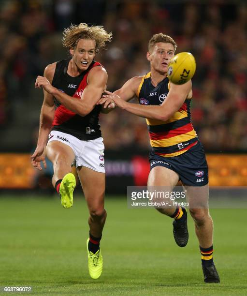 Darcy Parish of the Bombers is tackled by Rory Laird of the Crows during the 2017 AFL round 04 match between the Adelaide Crows and the Essendon...
