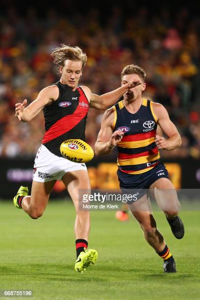 Darcy Parish of the Bombers kicks the ball in front of Rory Laird of the Crows during the round four AFL match between the Adelaide Crows and the...