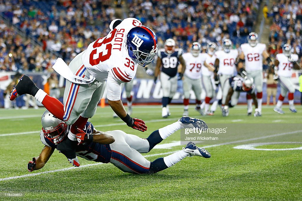 Da'Rel Scott #33 of the New York Giants is tackled by Logan Ryan #26 of the New England Patriots in the second half during the preseason game at Gillette Stadium on August 29, 2013 in Foxboro, Massachusetts.