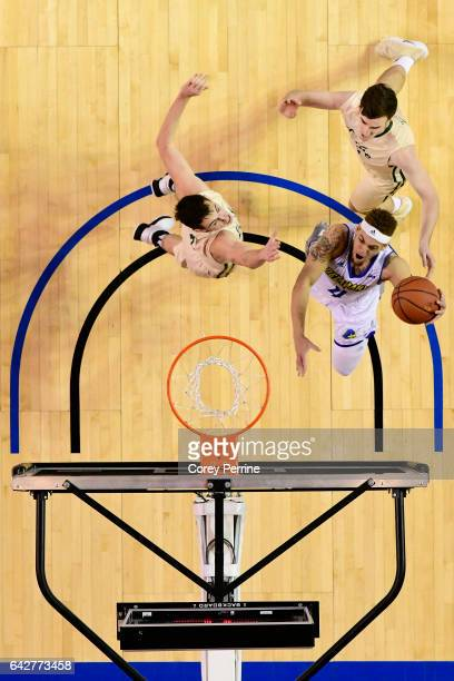 Darian Bryant of the Delaware Fightin Blue Hens scores against Omar Prewitt of the William Mary Tribe as teammate Jack Whitman of the William Mary...