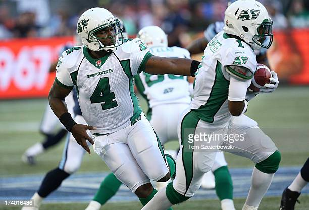 Darian Durant of the Saskatchewan Roughriders hands the ball off to Kory Sheets during CFL game action against the Toronto Argonauts on July 11 2013...
