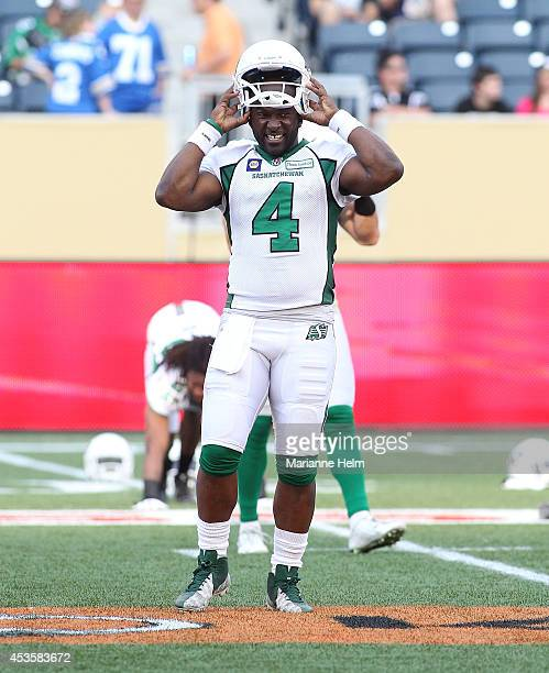 Darian Durant of the Saskatchewan Roughriders puts on his helmet as he warms up on the field before a CFL game against the Winnipeg Blue Bombers at...