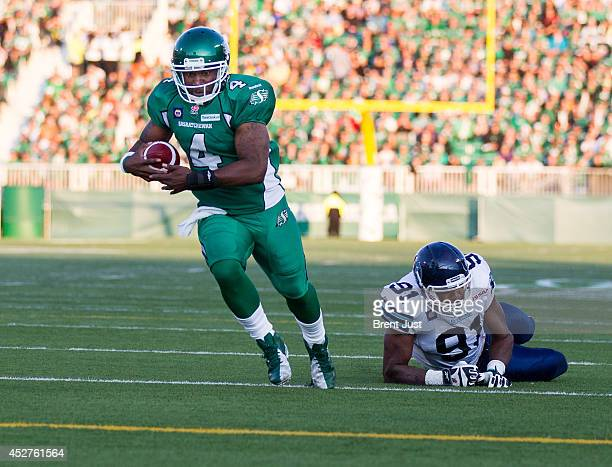 Darian Durant of the Saskatchewan Roughriders runs in for a touchdown after Tristan Okpalaugo of the Toronto Argonauts misses a tackle in a game...