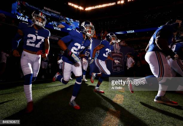 Darian Thompson Michael Hunter Jr #23 and Andrew Adams of the New York Giants run onto the field before their game against the Detroit Lions at...