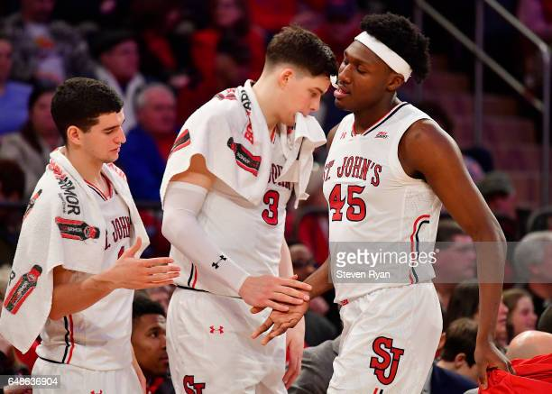 Darien Williams of the St John's Red Storm is greeted by his teammates Federico Mussini and Amar Alibegovic after fouling out against the Providence...