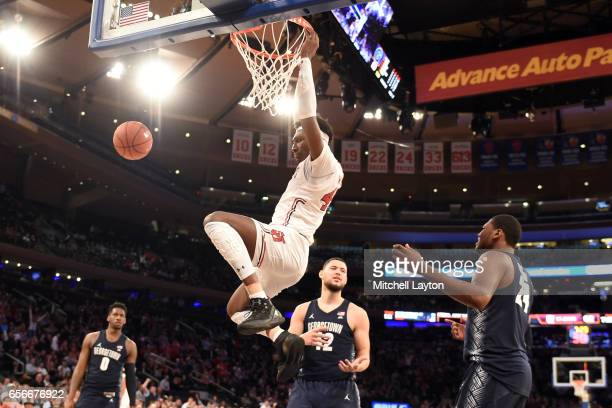 Darien Williams of the St John's Red Storm makes a jam during the Big East Basketball Tournament First Round game against the Georgetown Hoyas at...