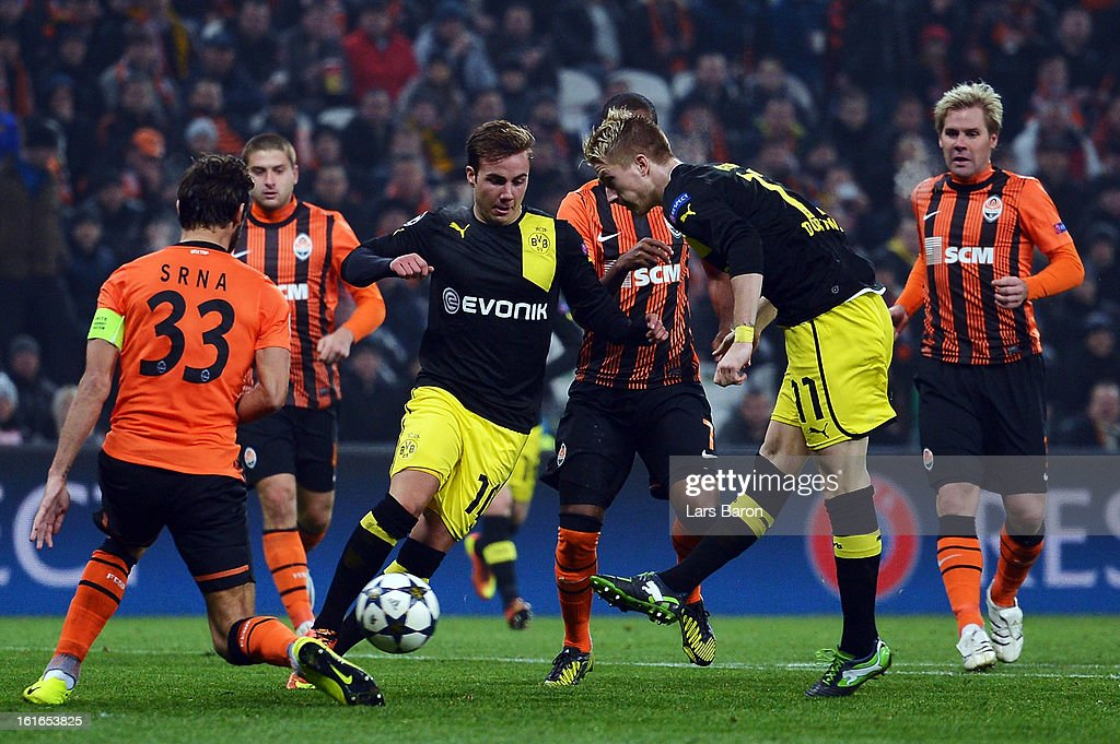 Darijo Srna and Tomas Hubschman of Donetsk challenge Mario Goetze and Marco Reus of Dortmund during the UEFA Champions League Round of 16 first leg match between Shakhtar Donetsk and Borussia Dortmund at Donbass Arena on February 13, 2013 in Donetsk, Ukraine.