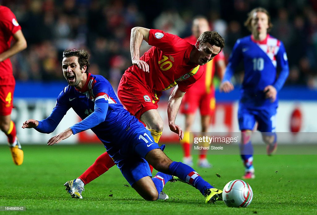 <a gi-track='captionPersonalityLinkClicked' href=/galleries/search?phrase=Darijo+Srna&family=editorial&specificpeople=546578 ng-click='$event.stopPropagation()'>Darijo Srna</a> of Croatia is brought down by the tackle from <a gi-track='captionPersonalityLinkClicked' href=/galleries/search?phrase=Andy+King+-+Giocatore+di+calcio+-+Classe+1988&family=editorial&specificpeople=14622523 ng-click='$event.stopPropagation()'>Andy King</a> of Wales during the FIFA 2014 World Cup qualifier between Wales and Croatia at The Liberty Stadium on March 26, 2013 in Swansea, Wales.