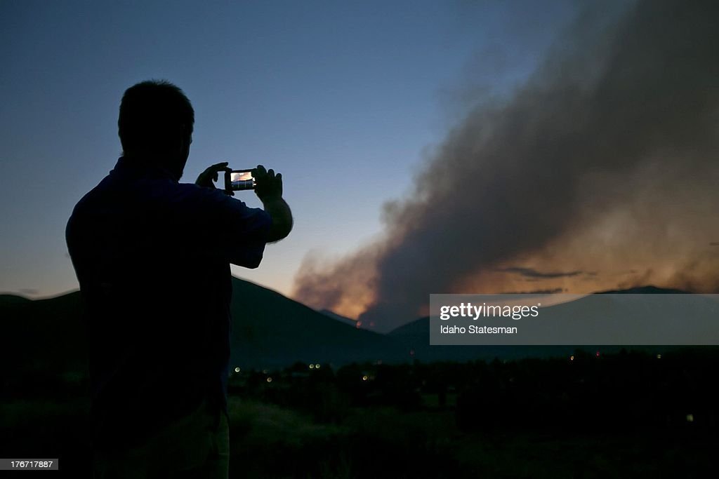 Darin D. Sales of Hailey, Idaho, takes photos of the Beaver Creek Fire looming above the Wood River Valley town, Saturday, August 17, 2013.
