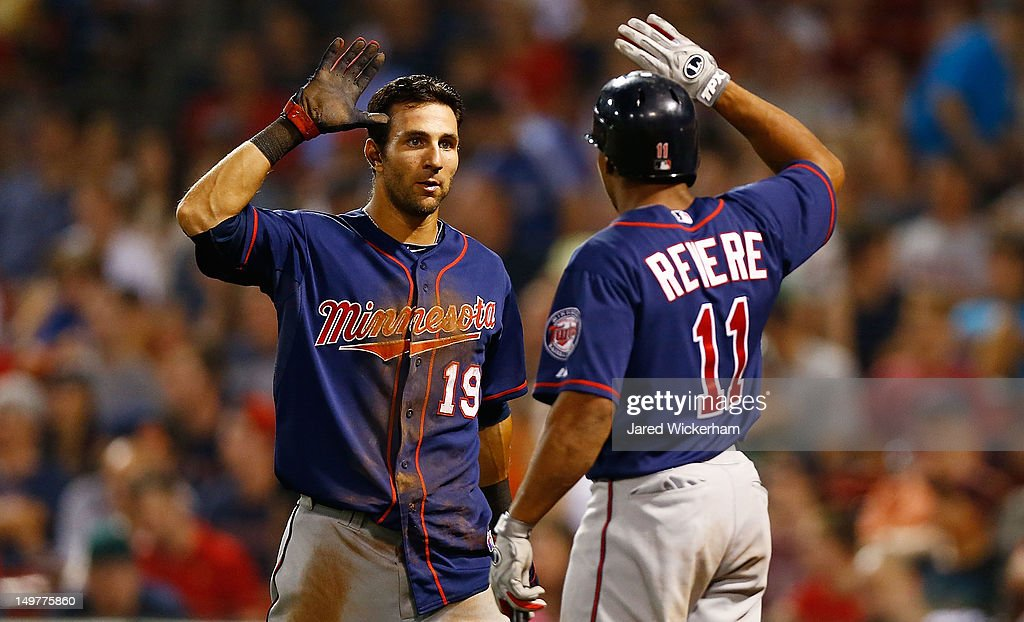 Darin Mastroianni #19 of the Minnesota Twins is congratulated by teammate Ben Revere #11 after scoring in the 10th inning against the Boston Red Sox during the game on August 3, 2012 at Fenway Park in Boston, Massachusetts.