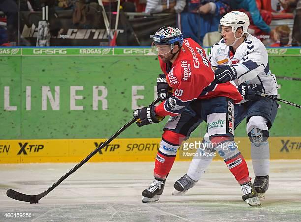 Darin Olver of the Eisbaeren Berlin handles the puck against Sam Klassen of the Hamburg Freezers during the DEL Ice Hockey match between Eisbaeren...