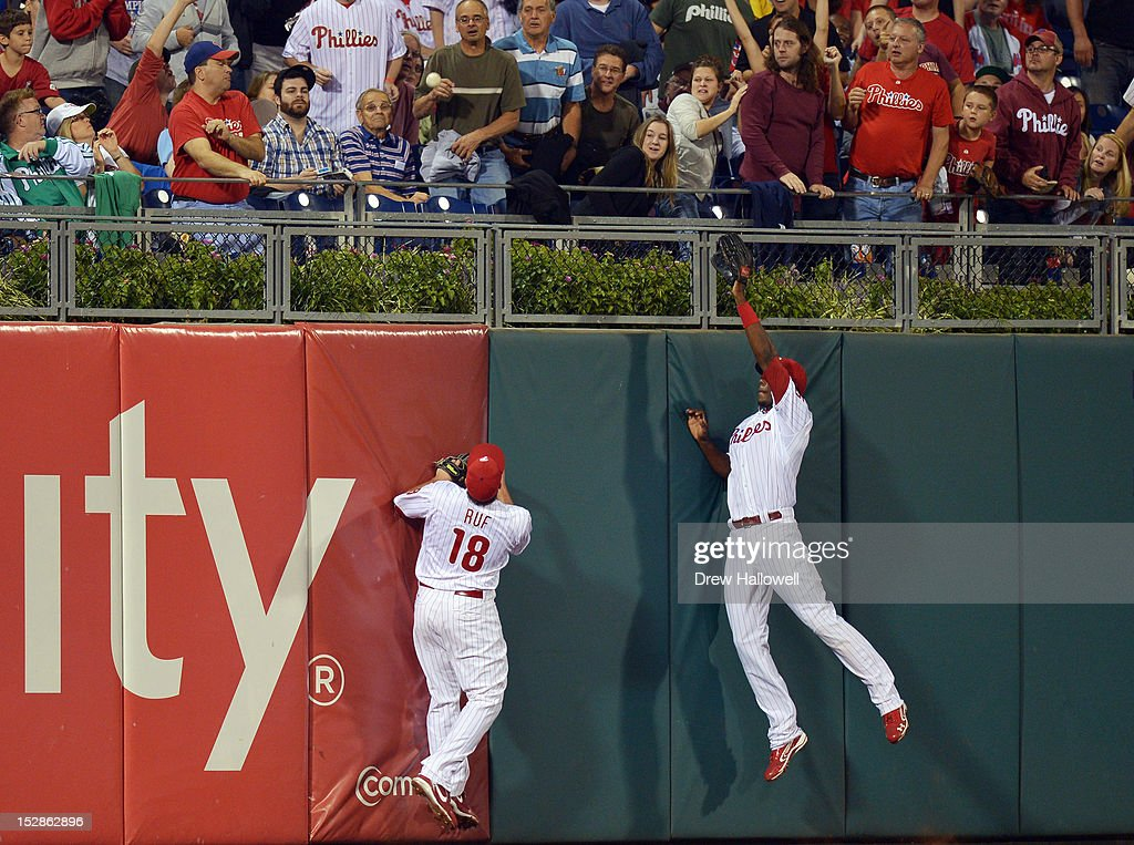 Darin Ruf #18 and John Mayberry Jr. #15 of the Philadelphia Phillies jump for a home run ball hit by Michael Morse #38 (not pictured) of the Washington Nationalsat Citizens Bank Park on September 27, 2012 in Philadelphia, Pennsylvania.