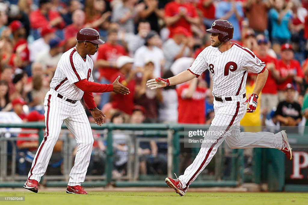 Darin Ruf #18 of the Philadelphia Phillies is congratulated by third base coach Juan Samuel #8 as he round the bases after hiting a solo home run in the second inning of the game against the Arizona Diamondbacks at Citizens Bank Park on August 23, 2013 in Philadelphia, Pennsylvania.