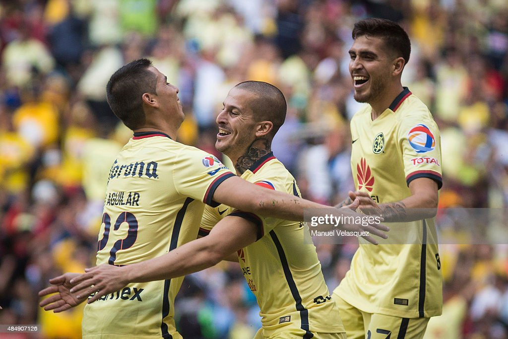 Dario Benedetto (C) celebrates with teammates <a gi-track='captionPersonalityLinkClicked' href=/galleries/search?phrase=Paul+Aguilar&family=editorial&specificpeople=4476672 ng-click='$event.stopPropagation()'>Paul Aguilar</a> (L) and Alvarado Ventura (R) of America after scoring the third goal of his team during a 6th round match between America and Veracruz as part of Apertura 2015 Liga MX at Azteca Stadium on August 22, 2015 in Mexico City, Mexico.