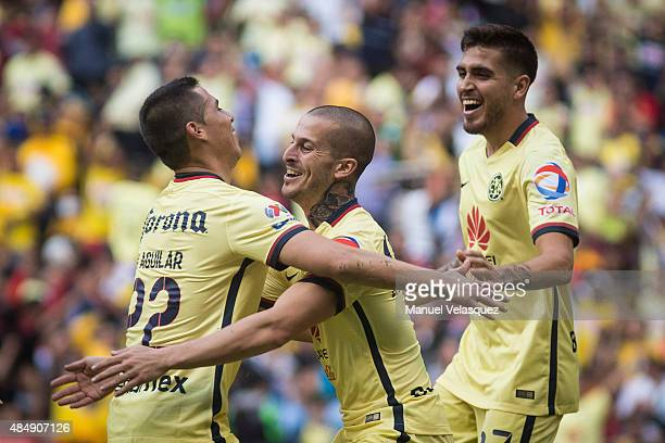 Dario Benedetto celebrates with teammates Paul Aguilar and Alvarado Ventura of America after scoring the third goal of his team during a 6th round...