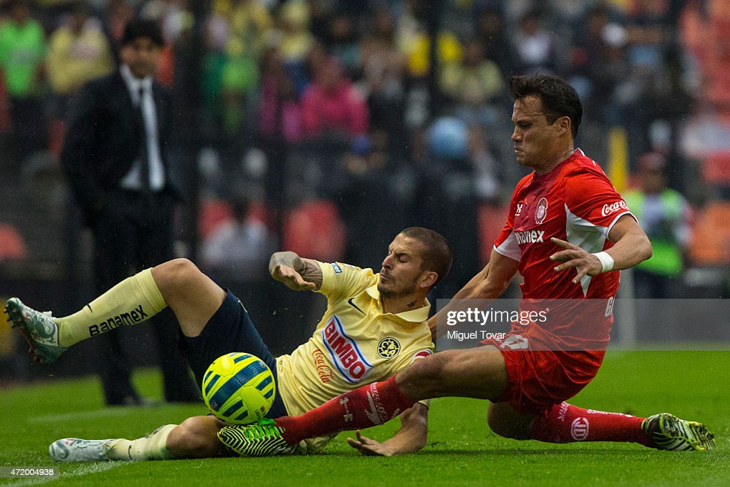 Dario Benedetto of America fights for the ball with <a gi-track='captionPersonalityLinkClicked' href=/galleries/search?phrase=Aaron+Galindo&family=editorial&specificpeople=771464 ng-click='$event.stopPropagation()'>Aaron Galindo</a> of Toluca as part of 16th round of Clausura 2015 Liga MX at Azteca Stadium on May 02, 2015 in Mexico City, Mexico.