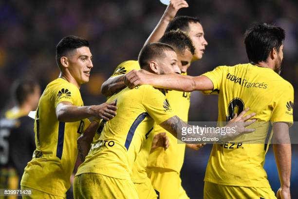 Dario Benedetto of Boca Juniors celebrates with teammates after scoring the third goal of his team during a match between Boca Juniors and Olimpo as...