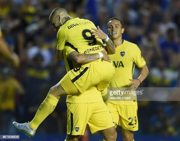 Dario Benedetto of Boca Juniors celebrates with teammates Cristian Pavon and Leonardo Jara after scoring the third goal of his team during a match...