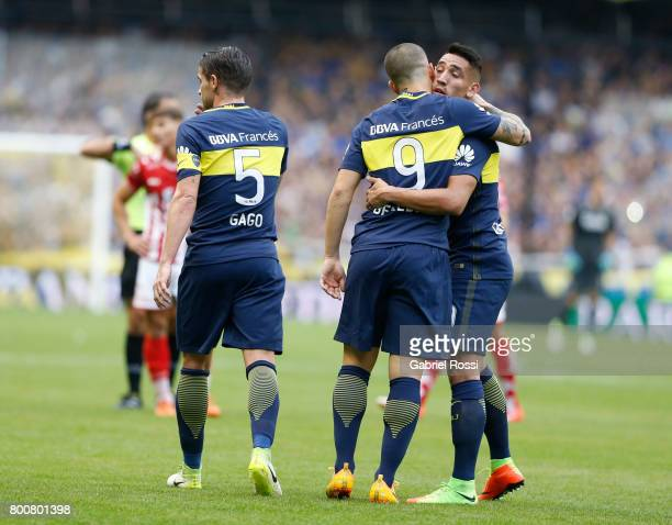 Dario Benedetto of Boca Juniors celebrates with teammates Fernando Gago and Ricardo Centurion after scoring the first goal of his team during a match...