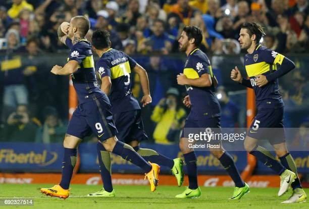 Dario Benedetto of Boca Juniors celebrates with teammates Pablo Perez and Fernando Gago after scoring the first goal of his team during a match...