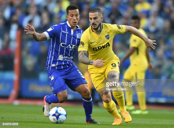 Dario Benedetto of Boca Juniors fights for the ball with Juan Andrada of Godoy Cruz during a match between Boca Juniors and Godoy Cruz as part of...