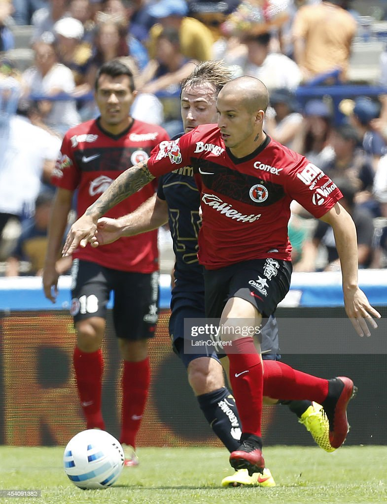 Dario Benedetto of Xolos Tijuana figths for the ball with Martin Romagnoli of Pumas UNAM during a match between Pumas UNAM and Xolos Tijuana as part of 6th round Apertura 2014 Liga MX at Olimpic Stadium on August 24, 2014 in Mexico City, Mexico.