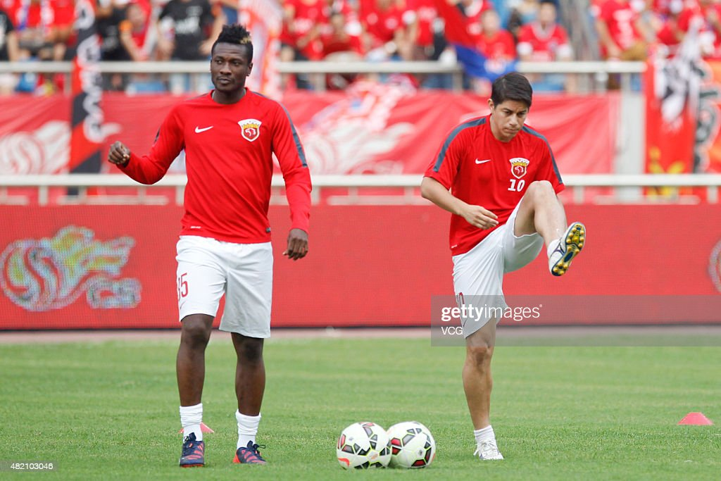 Dario Conca and Asamoah Gyan of Shanghai SIPG warm up prior to the CSL Chinese Football Association Super League match between Chongqing Lifan and...