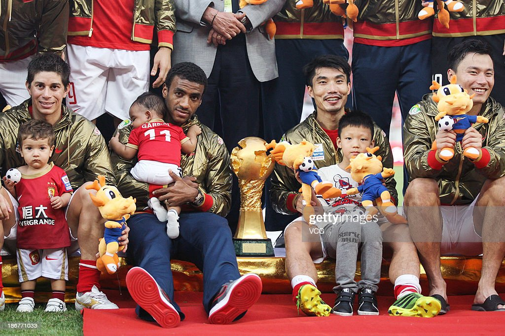 Dario Conca, Muriqui, Zheng Zhi and Gao Lin of Guangzhou Evergrande, with their sons, celebrate after defeating Wuhan Zall to win the 2013 Chinese Super League title at Tianhe Sports Center on November 3, 2013 in Guangzhou, China.