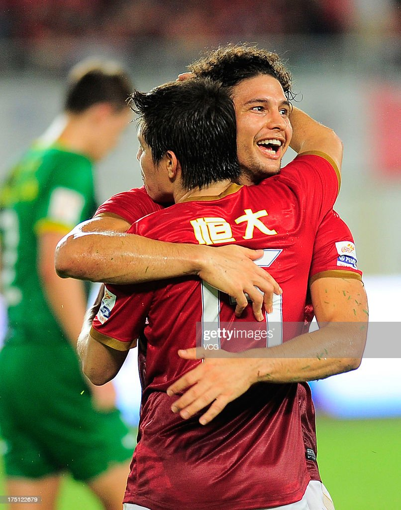 Dario Conca of Guangzhou Evergrande celebrates with teammate Elkeson after scoring their team's second goal with a penaltykick during the Chinese...