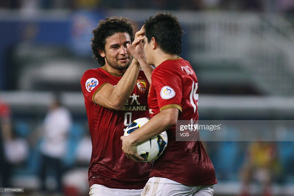 Dario Conca of Guangzhou Evergrande celebrates with teammate Elkeson after scoring his team's first goal with a penaltykick during the AFC Champions...