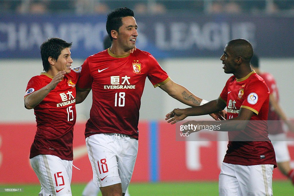 Dario Conca of Guangzhou Evergrande celebrates with teammates Lucas Barrios and Muriqui after scoring his team's first goal during the AFC Champions...