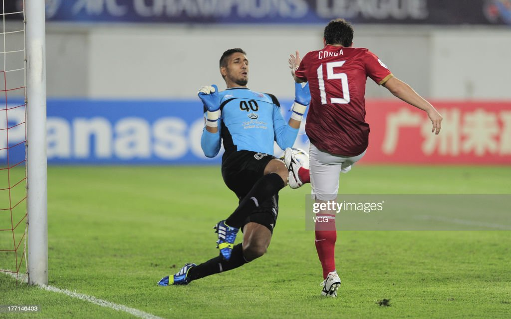 Dario Conca of Guangzhou Evergrande shoots the ball against goalkeeper Amine Lecomte of Lekhwiya during the AFC Champions League quarterfinal match...