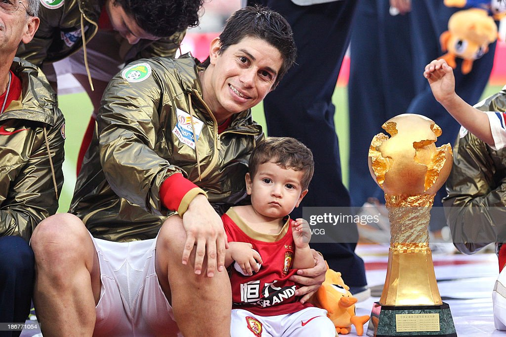 Dario Conca of Guangzhou Evergrande with his son celebrates with the trophy after defeating Wuhan Zall to win the 2013 Chinese Super League title at...