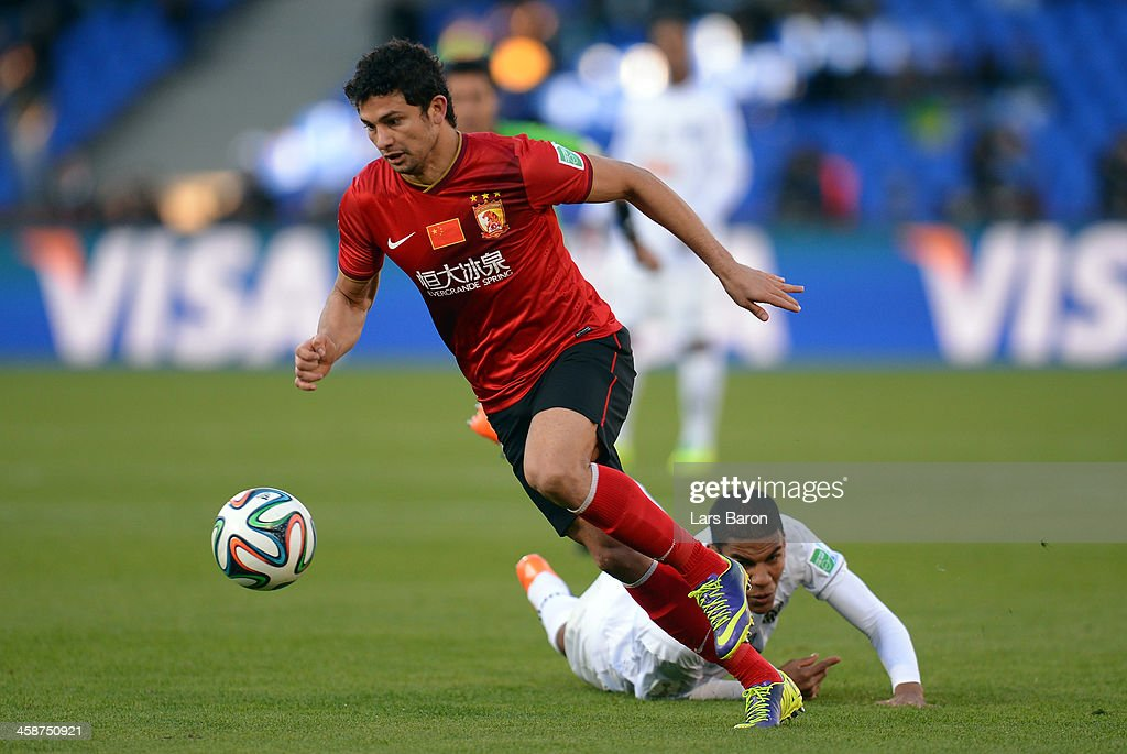 Dario Conca of Guangzhou is challenged by Leonardo Silva of Mineiro during the FIFA Club World Cup 3rd Place Match between Guangzhou Evergrande FC...